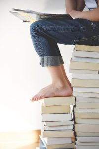 Person sitting on a pile of books